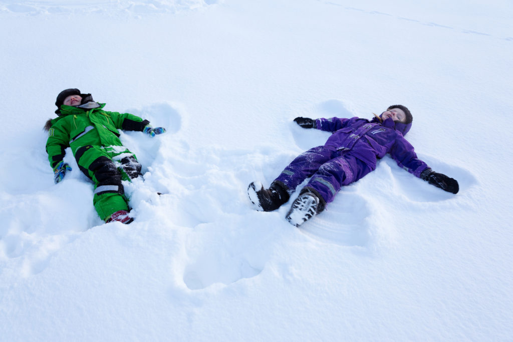 small kinds doing snow angels