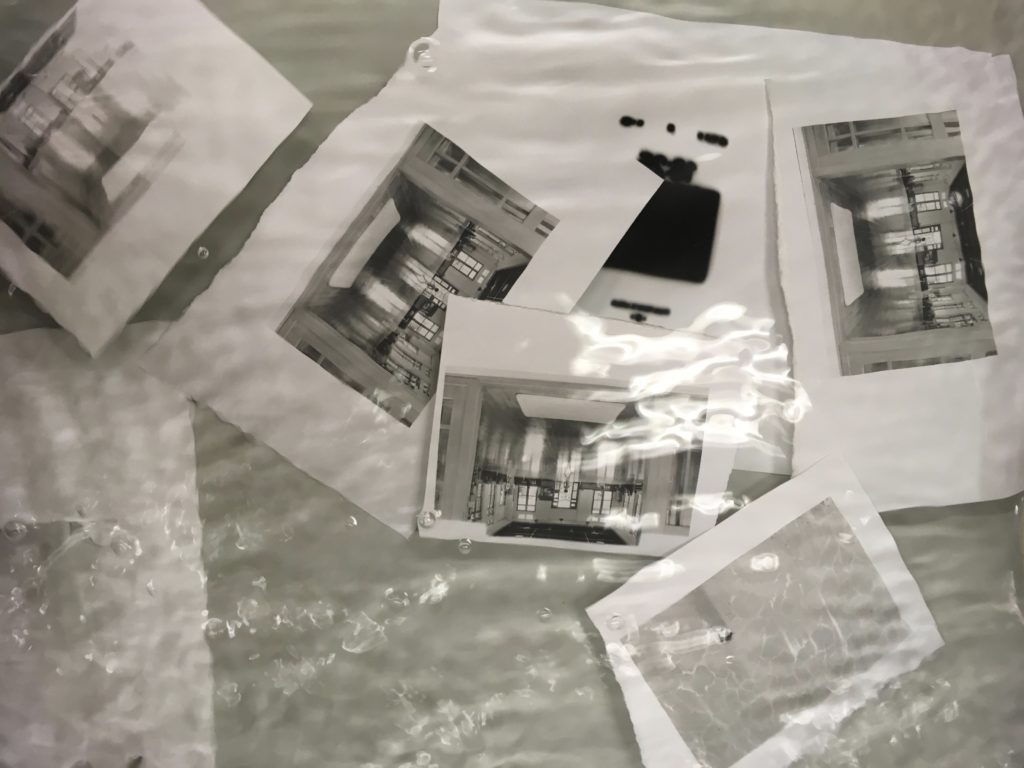 Washing chemicals off black and white prints in the darkroom.
