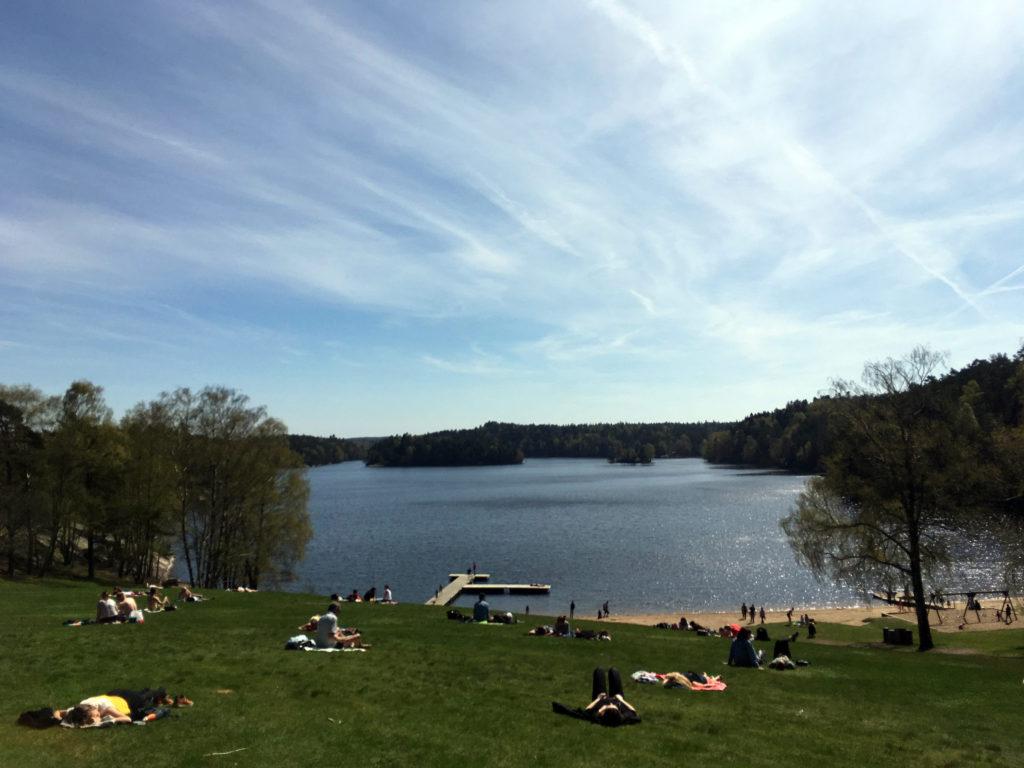 People sunbathing by the lake at Delsjön