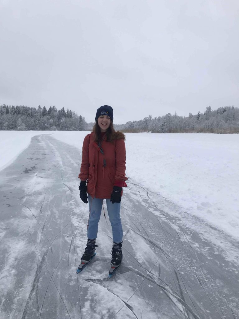Woman standing with ice skates on on frozen lake