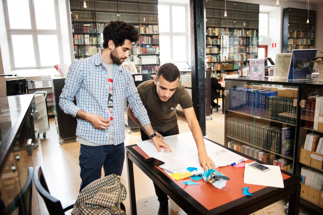 Two people working together in a llibrary