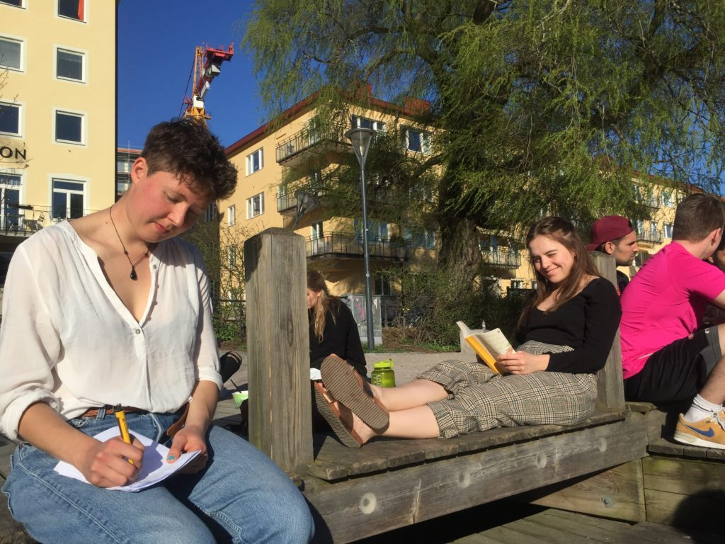 Friends studying by a river