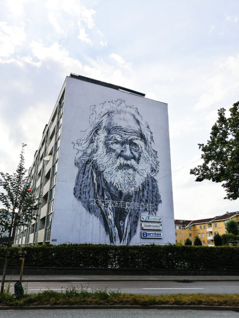 """Realistic black and white mural of elderly man with text """"Moments of Life"""""""
