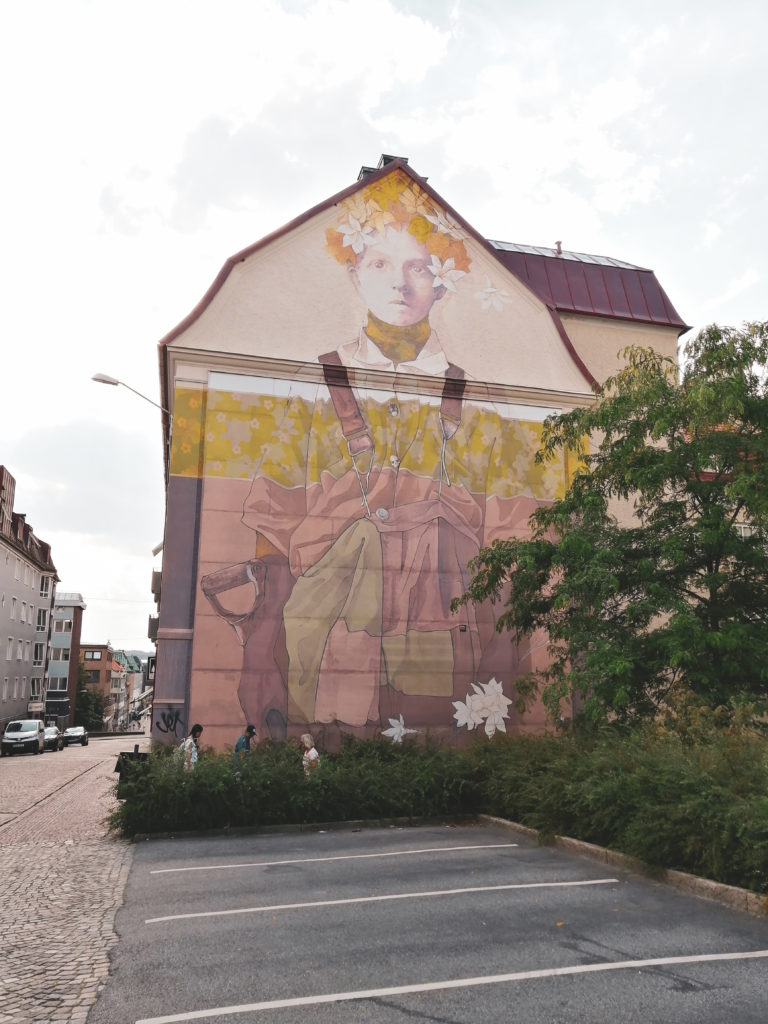 Washed out mural of person wearing dungarees and flower crown