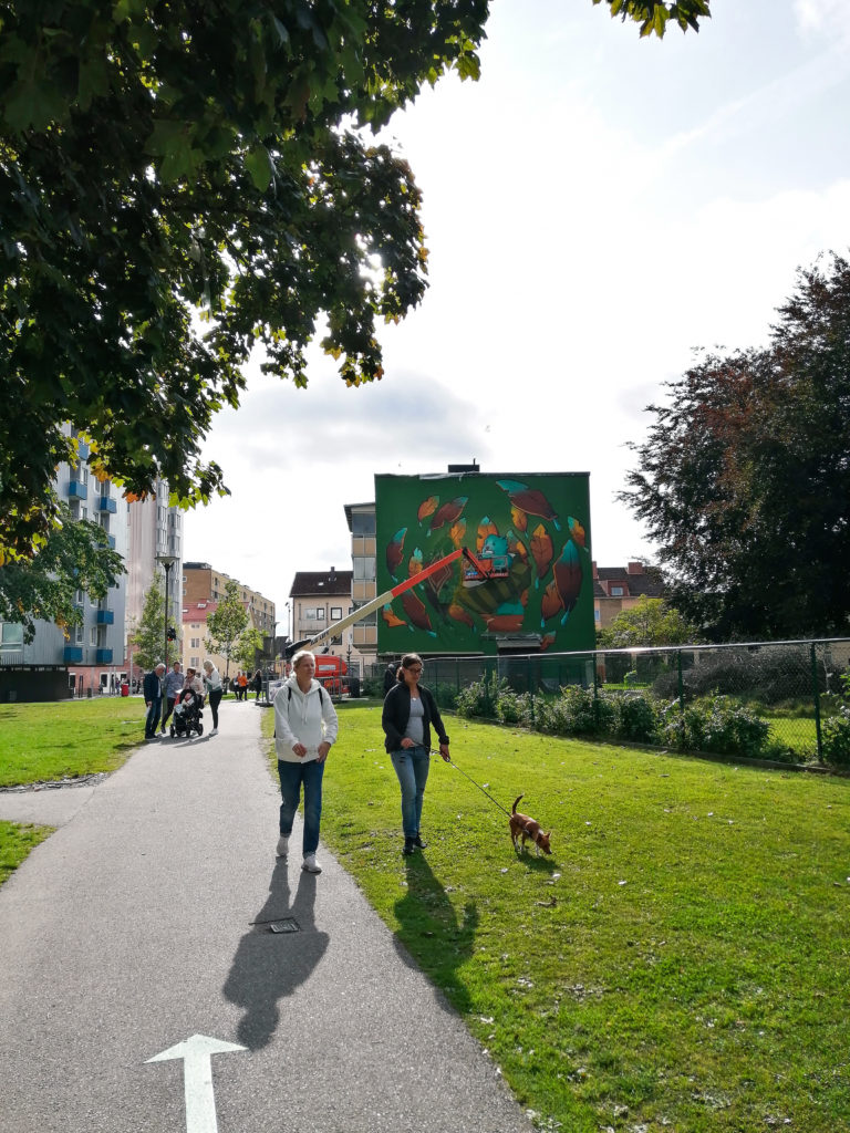 Women walking a dog in front of mural in Norrby