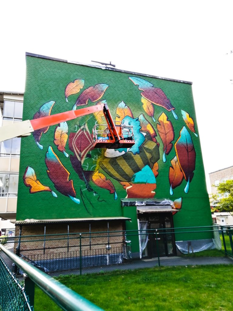 Colourful and animated mural of character riding a teacup surrounded by glowing leaves