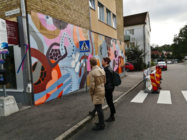 People standing and looking at a mural