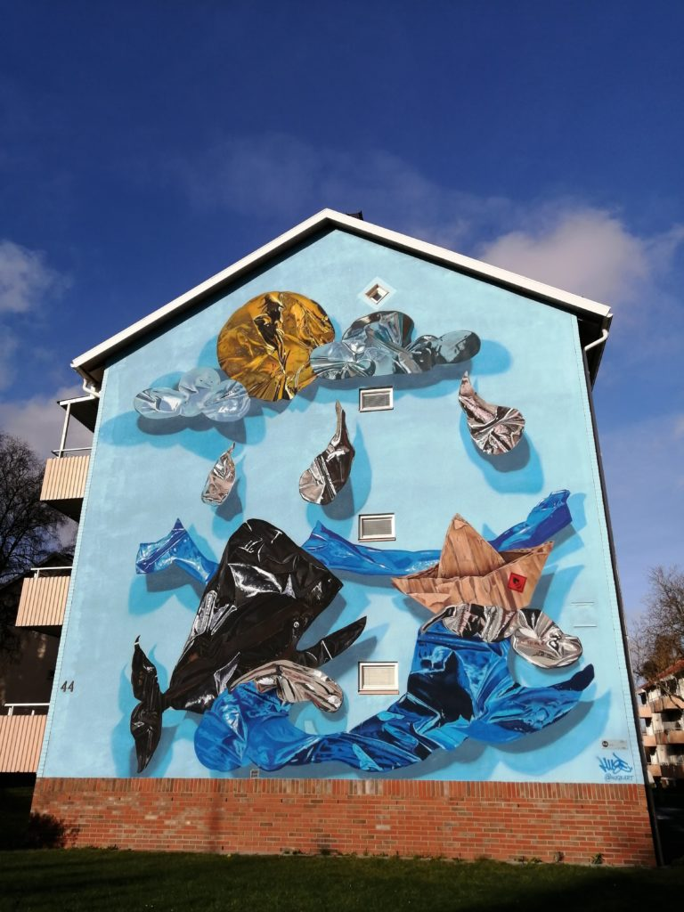 Mural of hyper-realistic balloon whale swimming in litter