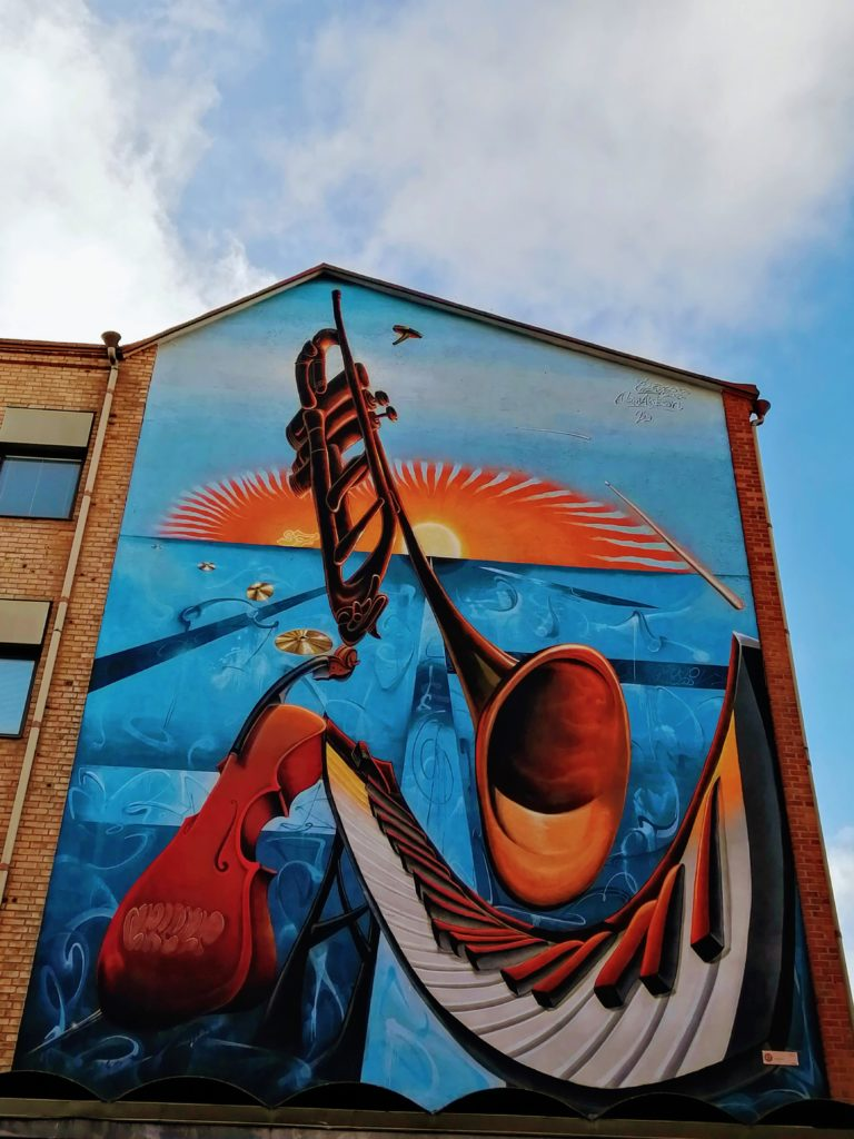 Bright blue and orange mural of musical instruments at sunset