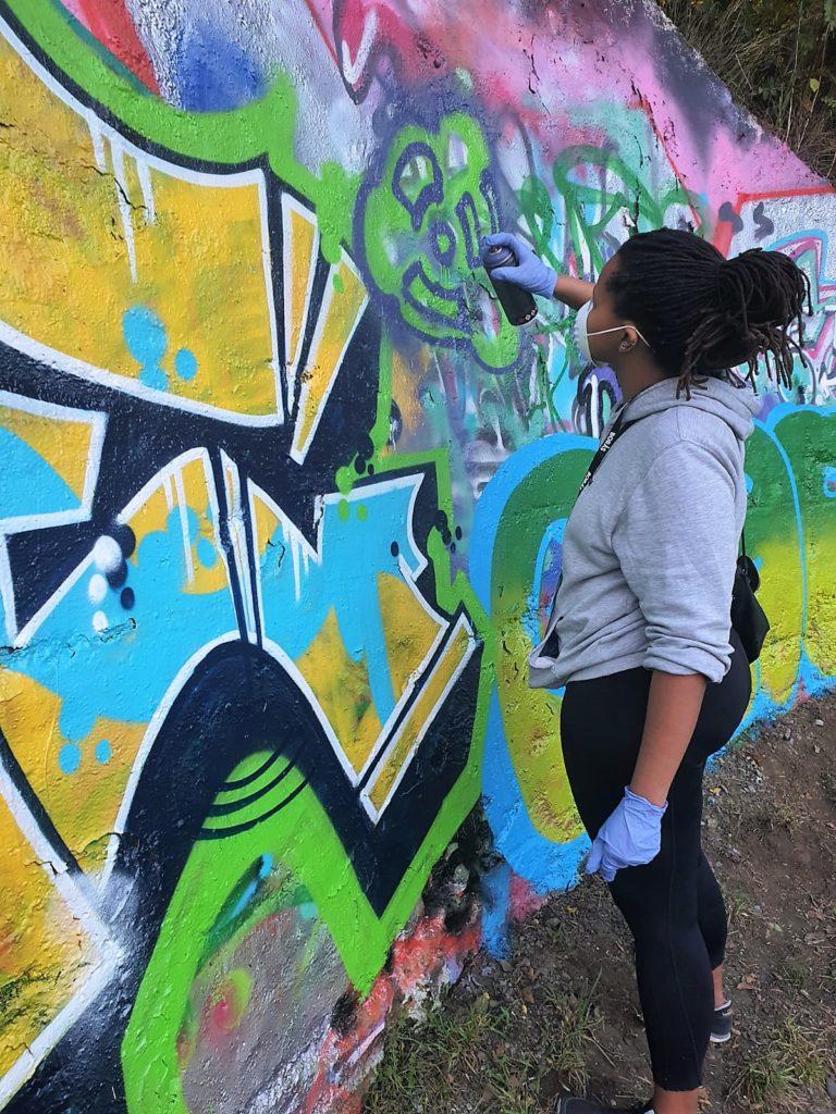 Woman spray painting on graffiti wall