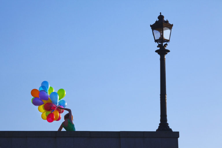 Person holds rainbow balloons