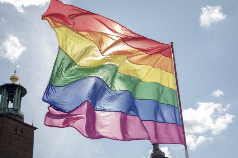Pride flag waves in front of blue sky in Stockholm